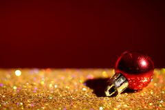 Golden paillettes and Christmas ball against color background royalty free stock photo