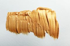 Golden paint brush strokes on white. Background stock photography