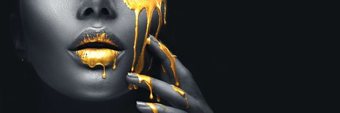 Golden paint smudges drips from the face lips and hand, golden liquid drops on beautiful model girl`s mouth, creative makeup