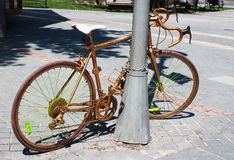 Golden painted bicycle chained to a street lamppost Stock Images