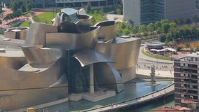 Golden painted building of Guggenheim Museum in Bilbao, people walking in square. Stock footage stock video