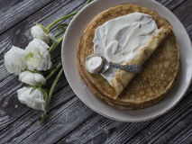 Golden pancakes with cream plate close-up dark background Ranunkulyus Stock Photos