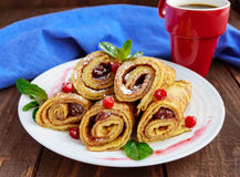 Golden pancakes in the form of roll with strawberry jam and powdered sugar. On a white plate on a wooden table. Close-up. Breakfast royalty free stock images
