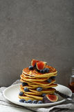 Golden pancakes with fresh fruits against concrete wall Stock Photos