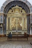 Golden panelling in Goa, India. Goa, India - January 2018:Lone worshipper at The S� Catedral de Santa Catarina Stock Image