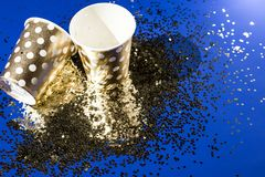 Golden paper cups for birthday party with golden confetti on blue background royalty free stock photography