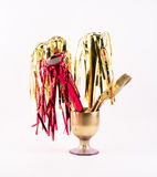 Golden party whistles with stripes, spatula and brush gathered in a golden glass Stock Image