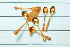 Golden pastry fork. Cake lifter, sugar spoons on a light blue wooden plate Stock Photos