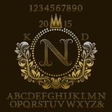 Golden patterned letters and numbers with initial monogram in coat of arms form. Elegant font and elements kit for logo design.  Royalty Free Stock Images