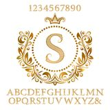 Golden patterned letters and numbers with initial monogram in coat of arms form. Shining font and elements kit for logo design.  Royalty Free Stock Photography
