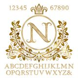 Golden patterned letters and numbers with initial monogram in coat of arms form. Shining font and elements kit for logo design.  Stock Image