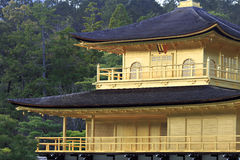 Golden Pavillion close up. Tightly cropped view of oriental pavillion with gold leaf covered walls and pine forest in the background royalty free stock photos