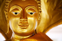 Golden peaceful Buddha statue smiling peaceful face. Religious yellow sculpture at Buddhist shrine in Thailand Royalty Free Stock Photos