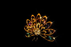 Golden Peacock. Gold and crystal peacock ornament on black velvet with star effect royalty free stock photo