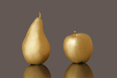 Golden pear and apple. On dark background Stock Photo
