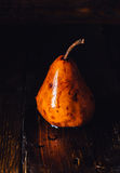 Golden Pear with Drops on Surface. On Table. Vertical royalty free stock photo