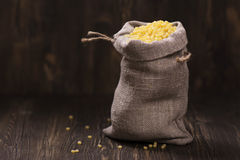 Golden pearl couscous in a burlap bag Royalty Free Stock Image