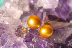 Golden pearl earrings on ametyst background. Pair of golden pearl earrings on ametyst background Stock Images