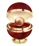 A golden pearl jewelry in a gift red box. A large gold golden pearl in a beautiful red gift round package with a gold design on a Stock Photos