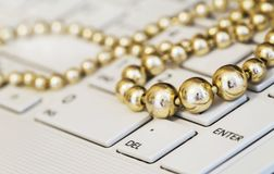 Golden pearls on a white keyboard Stock Photos