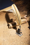 Golden pen and ancient manuscripts Royalty Free Stock Image