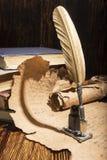Golden pen and ancient manuscripts Stock Photo