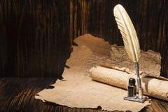 Golden pen and ancient manuscripts Stock Photos