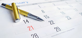 Golden Pen on Calendar. Closeup February 21 February international mother language day stock photo