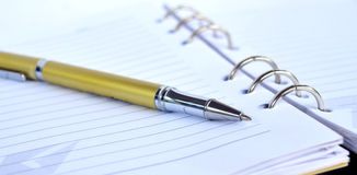 Golden Pen on note pad Royalty Free Stock Photo