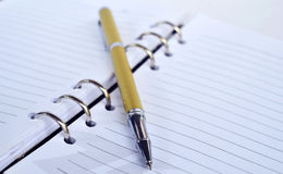 Golden Pen on note pad Stock Image