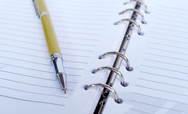 Golden Pen on note pad Stock Images