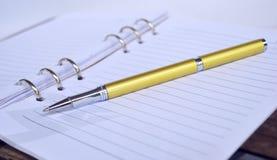 Golden Pen on note pad Stock Photo