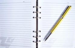 Golden Pen on note pad Stock Photos