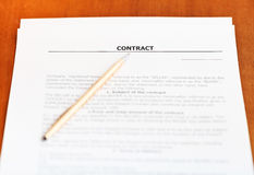 Golden pen on sheet of sales contract on table Stock Photos