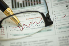 Golden pen showing diagram on financial report. Through reading glasses Stock Photography