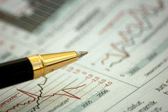Golden pen showing diagram on financial report.  Stock Image