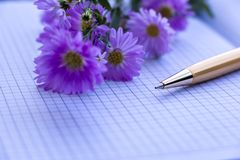 Golden Pen and Violet Flowers on Notebook stock photos