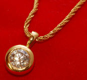 Golden pendant. A beautiful golden pendant with a diamond on red background Royalty Free Stock Photography