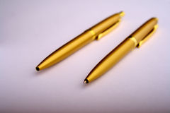 Golden pens Stock Images