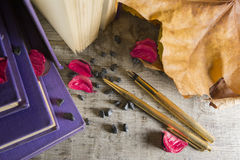 Golden pens and old books. On a wooden background stock photography