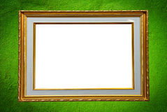 Golden photo frame on green wall. Golden wooden photo frame on Green grunge cement wall background Stock Photo