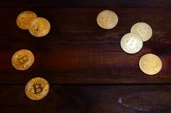 Golden physical bitcoins lies on dark wooden backgound, close up. High resolution photo. Cryptocurrency mining concep. T Stock Photos