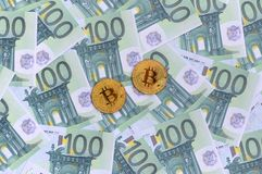 Golden physical bitcoins is lies on a set of green monetary deno Stock Photography