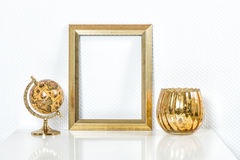 Golden picture frame with decorations. Mock up for your photo. Or text Vase and globe no name products royalty free stock photos