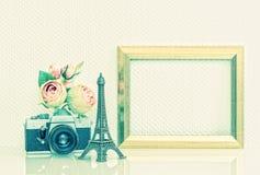 Golden picture frame, flowers and vintage camera. Nostalgic deco Stock Image