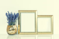 Golden picture frame and lavender flowers. Vintage style toned Stock Photography
