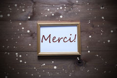 Golden Picture Frame With Merci Means Thank You And Snowflakes Stock Photography