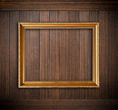 Golden picture frame on old dark wood background Royalty Free Stock Image