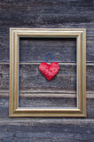 Golden picture frame on old wooden wall and heart Royalty Free Stock Images