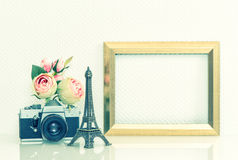 Golden picture frame, rose flowers and vintage camera. Eiffel To Royalty Free Stock Photography